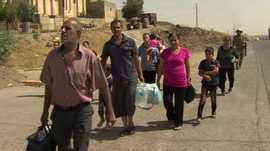 Christians fleeing mortar attacks in Iraq. (Pic: BBC)