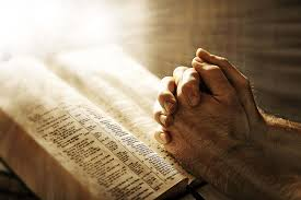 praying hands and light shining