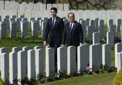 Prime Minister Justin Trudeau and French President walk through graves World War I soldiers